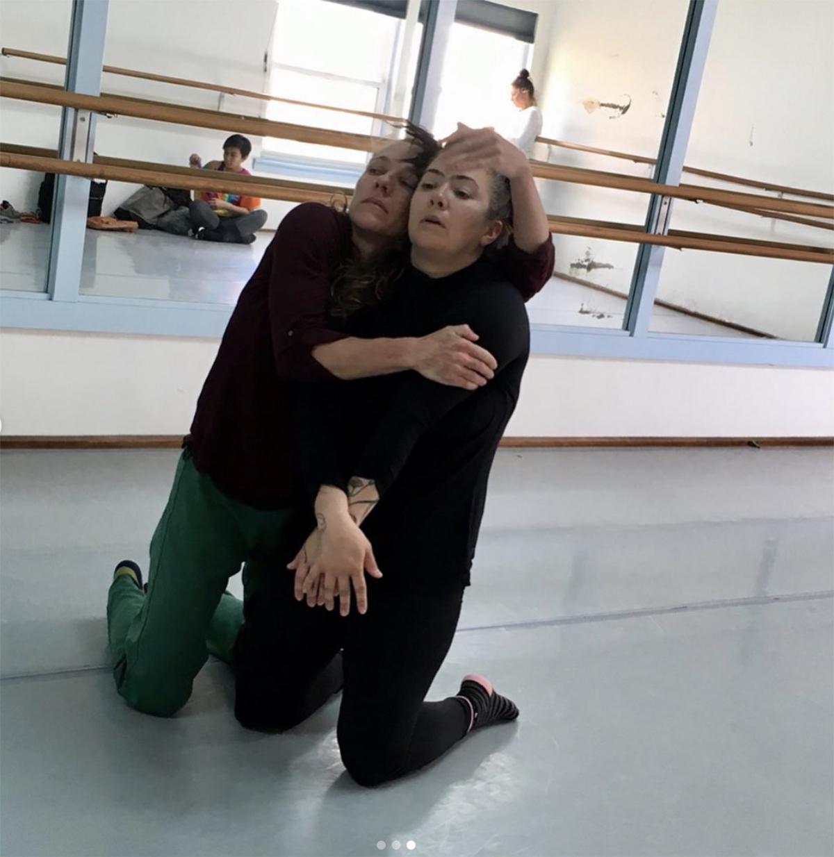 A dancer embraces another dancer.